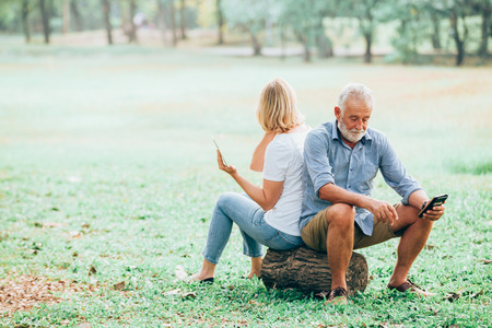 Senior couple using a tablet while sitting on wood in the park