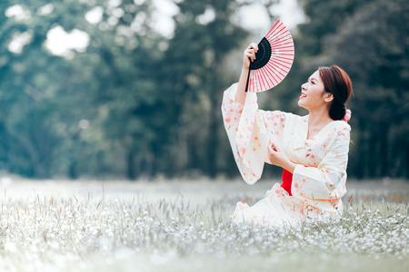 Asian young girl wearing a kimono in natural green grass.