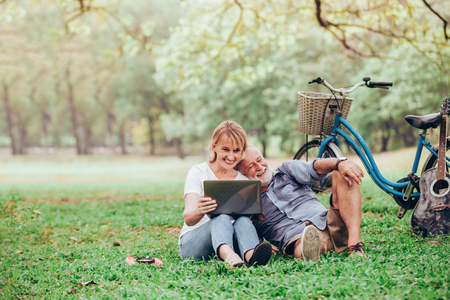 Senior couple using a laptop while sitting on grass in the park