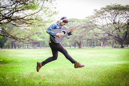 Asian young men jump in nature playing guitar and listen to music with headphones.