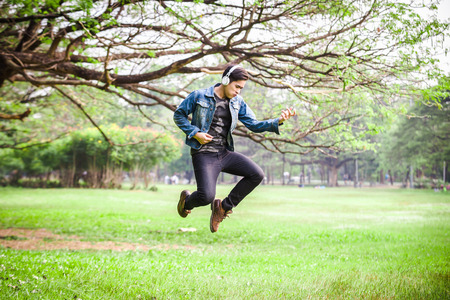 Asian young men jump in nature, listen to music with headphones. Stock Photo
