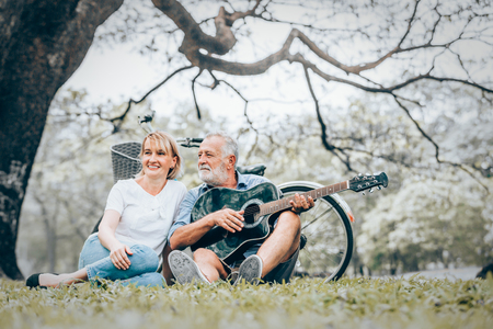 Senior couple in love playing acoustic song  guitar sitting on grass in the park Foto de archivo