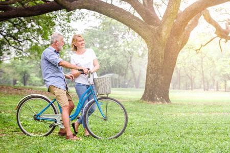 Ältere Paare , die ihr Fahrrad entlang glückliche Unterhaltung gehen