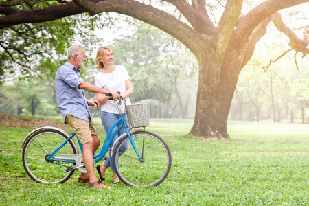 Senior couple walking their bike along happily talking happily. Stockfoto