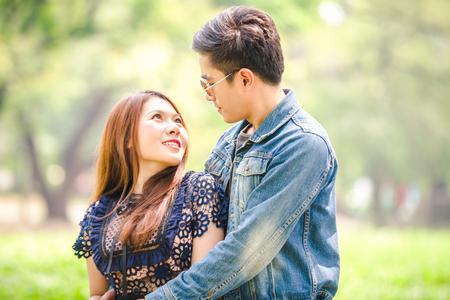 Portrait asian couple loving under tree in park Stock Photo
