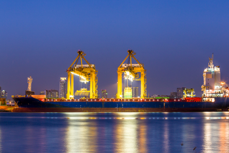 Shipping working loading containers by crane in ship on the night Stock Photo