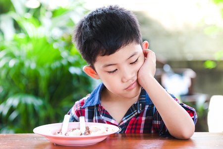 Asian little boy boring eating with rice food on the wooden table Stockfoto