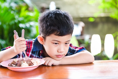Asian little boy boring eating with rice food on the wooden table Standard-Bild