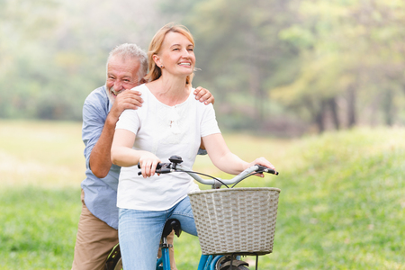 Senior couple walking their bike along happily talking happily. Banque d'images