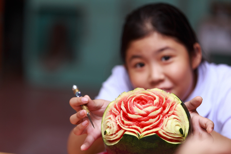 Asian little girl carve fruit in school