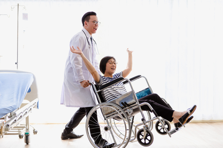 Asian men doctor caring about elderly woman in wheelchair,Happy, health concept Фото со стока