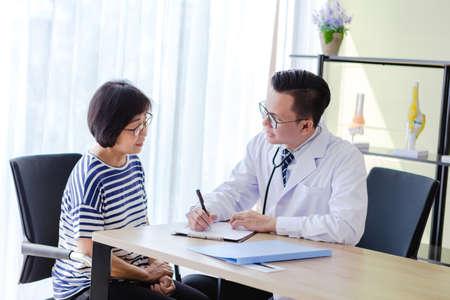 Oude geduldige vrouw in gesprek met arts Man in kantoor Stockfoto