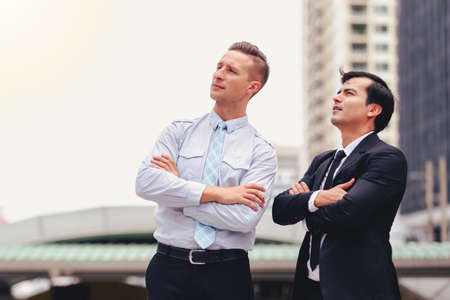 Two business men standing looking in city