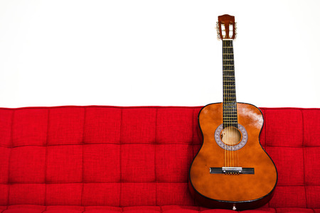 Furniture guitar on red sofa isolated white background Stock Photo