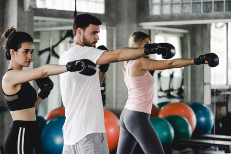 Sporty woman and men with the back boxing gloves training at the gym Stockfoto