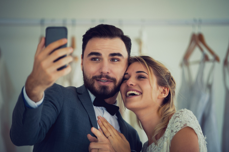 Beautiful model wedding couple holding smartphon online video call looking at screen,social networking