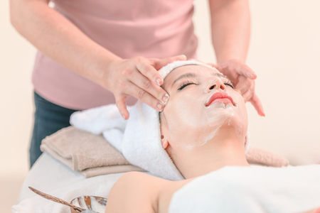 Beautiful young woman spa applying cosmetic cream on face relaxing receiving massage,Spa face concept