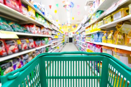 Zbliżenie kosz na zakupy zielony kolor z niewyraźnym tłem supermarketu