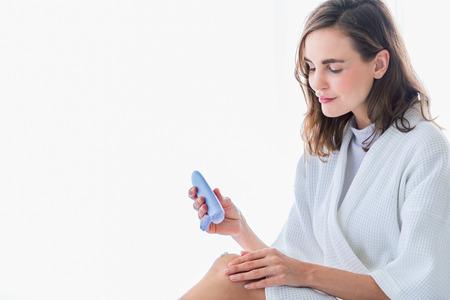 Frau, die erfrischende Creme oder Körperlotion auf ihre Beine und Hand aufträgt