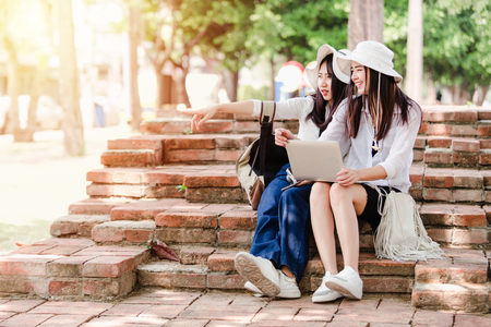 Asian young girls and friends Traveler in city,Two women sitting use laptop search for attractions