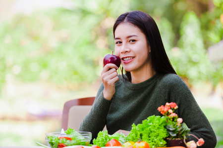 Asian beautiful young girl hold apple and eating salad vegetable outdoor , Concept healthy body