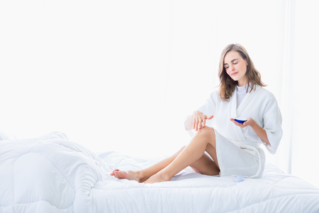 Woman applying refreshing cream or body lotion on her legs and hand