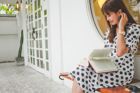 Beautiful Asian young women sitting reading book outdoor Reklamní fotografie