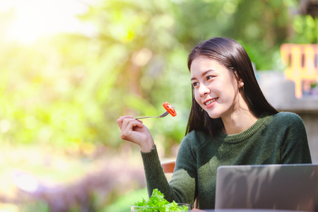 Asian beautiful young girl eating salad vegetable outdoor , Concept healthy body