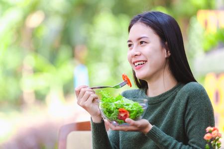 Asiatisches schönes junges Mädchen, das Salatgemüse im Freien isst, Konzept gesunder Körper