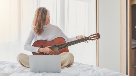 Beautiful young girl sitting playing guitar on bed in bedroom