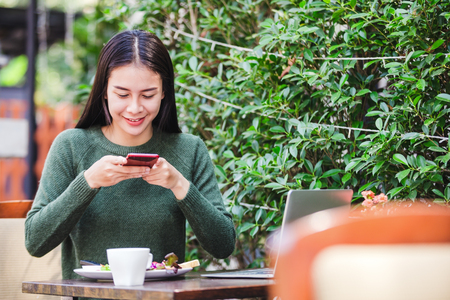 Asian young woman taking a photo of breakfast with smartphone social media Imagens
