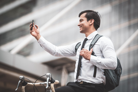 Business man riding bicycles in city,Standing call phone and selfie Reklamní fotografie