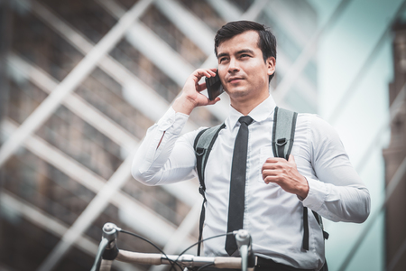 Business man riding bicycles in city,Standing call phone and selfie Imagens