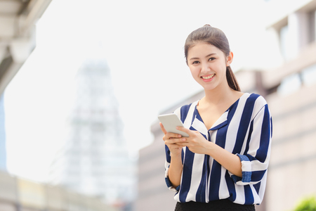 Outdoor lifestyle young woman looking on smartphone. Business concept Reklamní fotografie