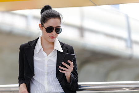 Outdoor lifestyle young businesswoman looking on smartphone. Business concept Imagens