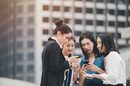 attractive asian businesswomen team playing smartphone outdoor city background Stock fotó