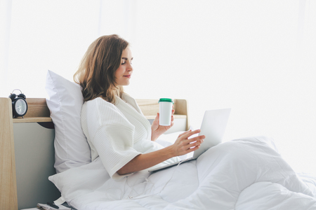 Woman typing work laptop on bed working in bedroom at home