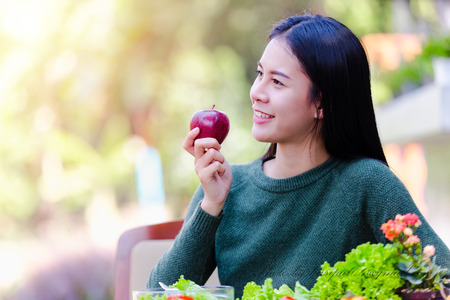 Asian beautiful young girl hold apple and eating salad vegetable outdoor , Concept healthy body Archivio Fotografico - 122269726