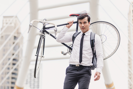 Business man worker carrying bicycle in city,Concept ecology bike go to worker Archivio Fotografico - 122269767