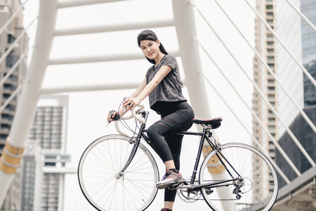 Lifestyle sport woman and health riding bike in city background