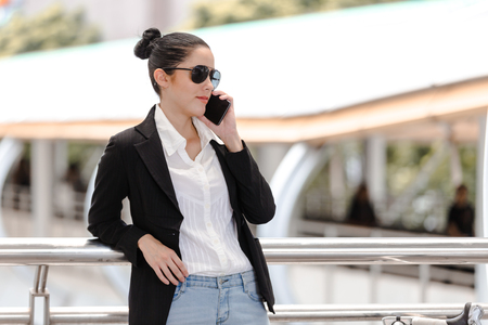 Outdoor young businesswoman worker talking on smartphone. Business concept