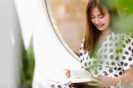 Beautiful Asian young women sitting reading book outdoor Imagens