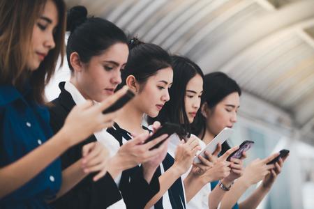attractive asian businesswomen team playing smartphone outdoor city background Stockfoto