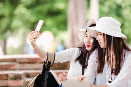 Asian young women tourists taking a selfie in city Archivio Fotografico - 122269910