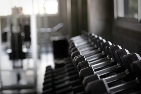 Background view back and white equipment dumbbells on rack in the gym sport center Archivio Fotografico - 122270040