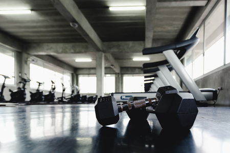 Background view back and white equipment dumbbells on floor in the gym sport center