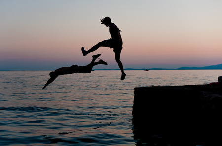 Boys jumping into the sea