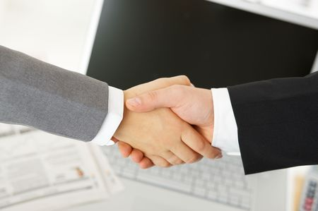 Handshake in the office over documents, computer in the background Stock Photo - 3814432