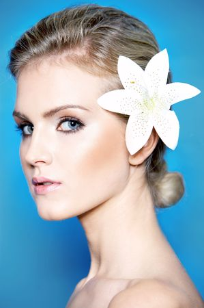 Portrait of a beautiful blonde woman with lily flower on a blue background photo