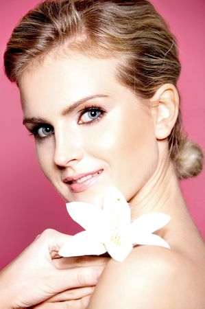 Portrait of a beautiful blonde woman with lily flower on a pink background photo